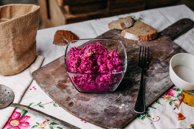 Вид спереди салат из свеклы пурпурный нарезанный грецкими орехами внутри прозрачной пластины соленый пряный витамин вкусные овощи на коричневом столе