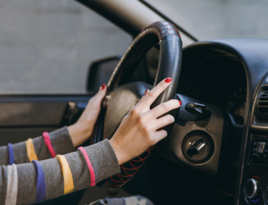 Молодая европейка со здоровой чистой кожей положила руки с красным маникюром на ногти на руль автомобиля с черным салоном. концепция путешествия и вождения