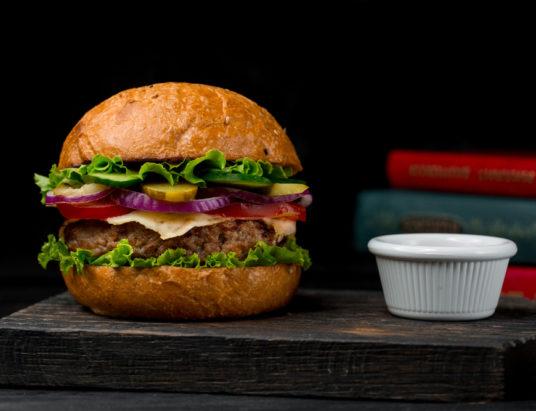 Бургер из говяжьей котлеты с соусом на деревянной доске