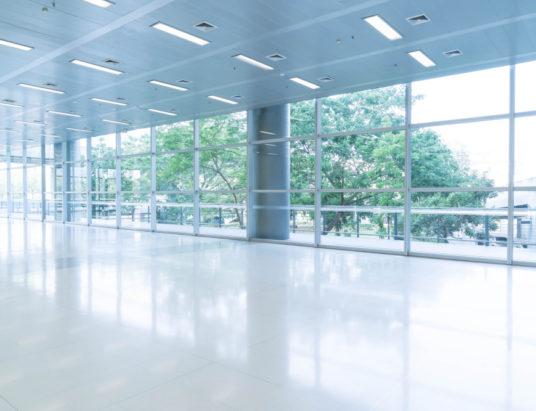 Размытый абстрактный фон, вид изнутри, глядя на пустой офисный вестибюль, входные двери и стеклянную ненесущую стену с рамкой
