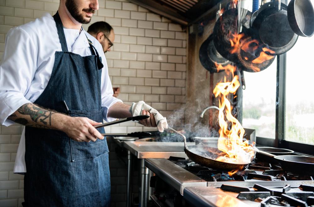 Шеф-повар готовит еду в кухне ресторана