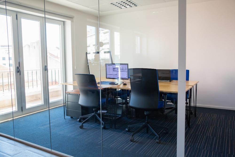 устой зал заседаний за стеклянной стеной. конференц-зал с конференц-столом, общий стол для команды и рабочих мест. торговые графики на мониторе. офисный интерьер
