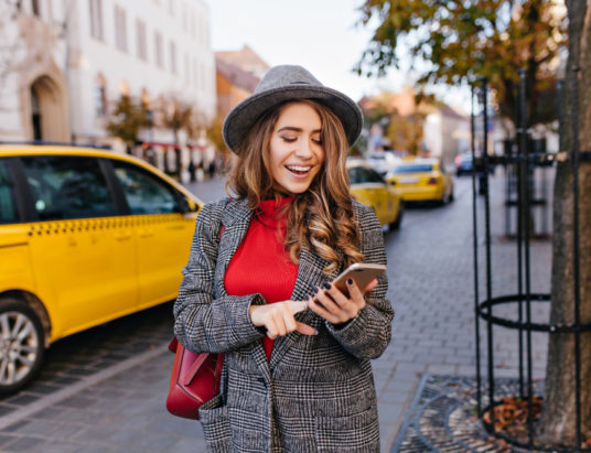 Красивая бизнес-леди отправляет текстовые сообщения во время прогулки по улице , такси