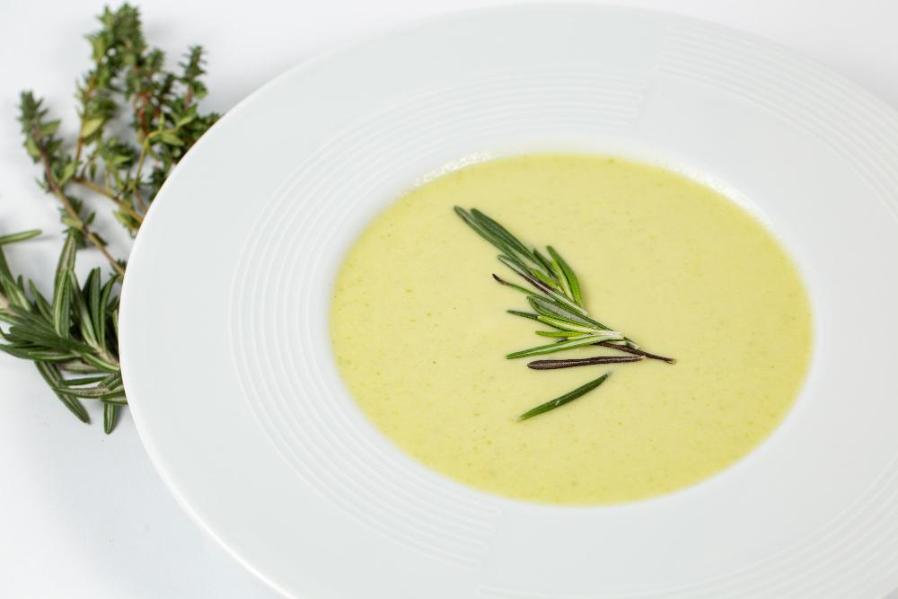 Снимок суповой тарелки с крем-супом из кабачков на белом столе, украшенном зелеными растениям