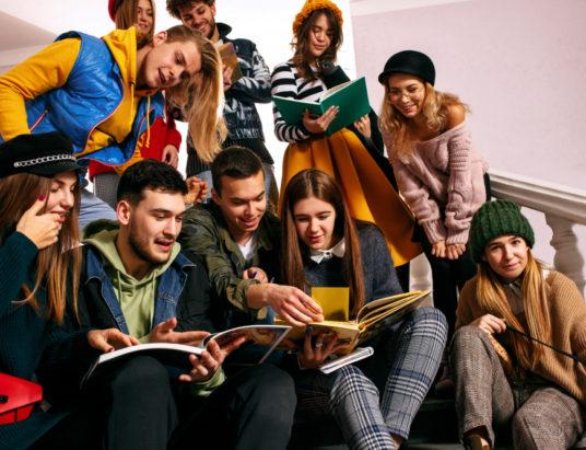 Группа веселых студентов сидит в аудитории перед уроком