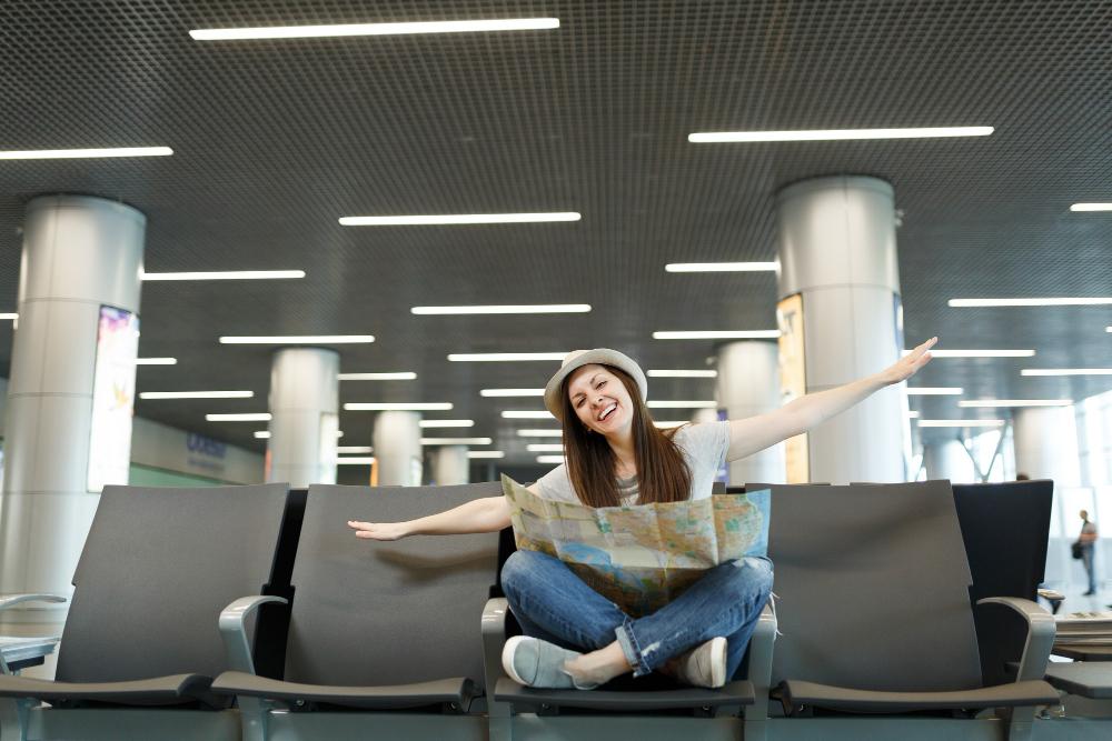 Молодая счастливая туристка-путешественница с бумажной картой сидит со скрещенными ногами, раздвинув руки, как в полете, ждет в холле вестибюля в аэропорту